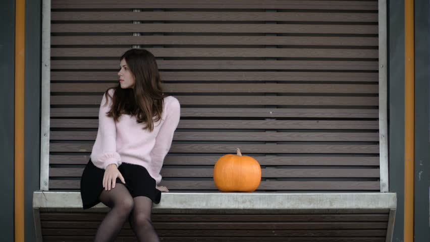 The girl is waiting for the tram at the bus stop. Pumpkin lies on the bench. Preparing for Halloween. Vegetarian lunch. Natural extracts for hair. Woman touches hair and vegetable. Station. 4K (UHD). | Shutterstock HD Video #1018857043