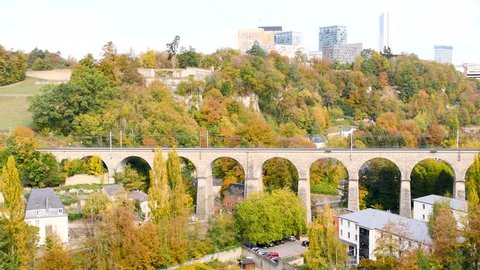 Landscape of the capital of Luxembourg. View on the business district of the city in the background. In the foreground, there is a large bridge over which a train passes.