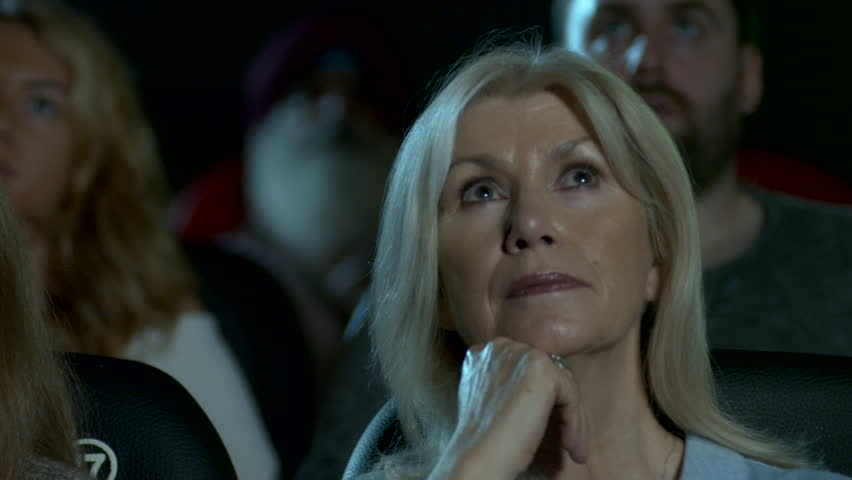 Senior woman watching a move at the movie theatre | Shutterstock HD Video #1018897573
