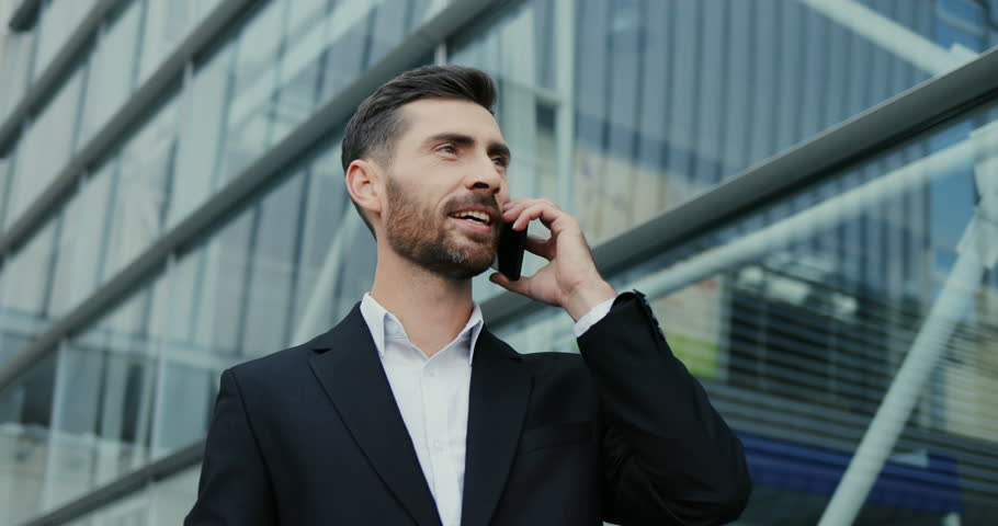 Portrait of the handsome smiled Caucasian businessman talking on the phone cheerfully and doing yes gesture with a hand. Close up. Outdoor. | Shutterstock HD Video #1018904473