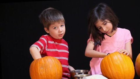 A young boy and girl clean out their Halloween pumpkins before carving them.  They sort seeds from innards.  The sister is focused, the boy goes slower.