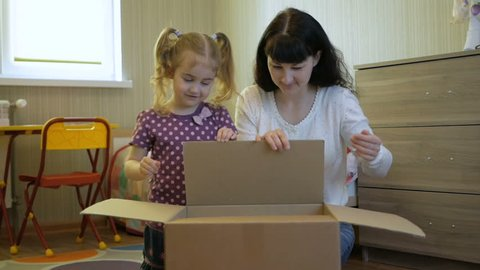 Family, Mom and Daughter opens the parcel from the online store. Young woman looks in the box, is surprised and happy to receive a surprise. Girl opened a box with a gift. Slow Motion.