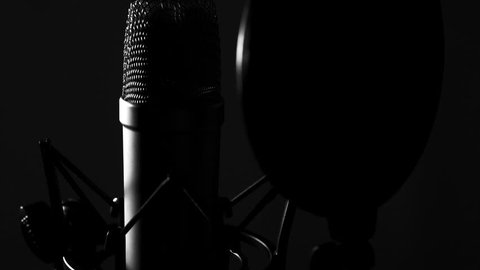 Large diaphragm condenser microphone in a music studio, lit with rembrandt lighting ing shot)