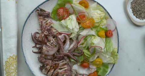 Top-down view of chef seasoning a plate of grilled octopus and salad with ground pepper and napkin. Closeup in 4k Phantom Flex camera. Chef's Table, Food network and cooking show inspired footage.