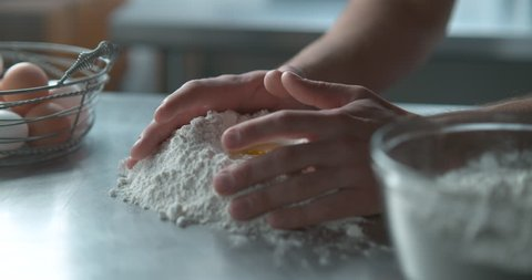 Pastry chef mixes a raw egg with flour on a metal counter top next to a metal basket of eggs and a bowl of flour, in soft light, in slow motion. Closeup shot in 4K on Phantom Flex