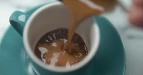 Barista pourring espresso in blue small cup in ultra slow motion closeup with 4k Phantom Flex camera.