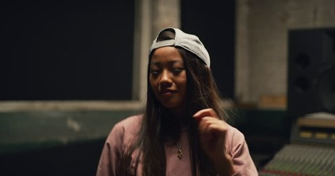 Funky dancer with long hair and backwards baseball cap in pink hoodie  dances in front of professional mixing board in studio. Medium shot on 4K RED camera.