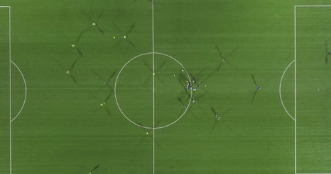 Top view with trail effect of soccer players running around the field.