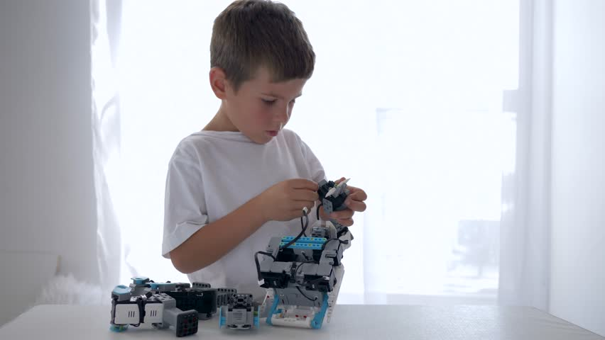 KHERSON, UKRAINE - OCTOBER 23, 2018: smart child boy repairs of robots parts with artificial intelligence closeup in bright room at home | Shutterstock HD Video #1019107363
