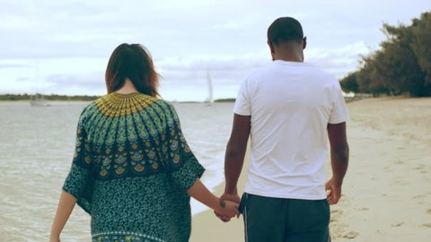 Young couple walking close to the shore holding hands and enjoying each other's company on the beach in Australia with soft day lighting. Medium shot on 4k RED camera.