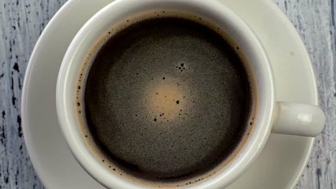 Top down slow motion shot of coffee rotating in a cup