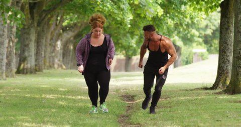 4K Fitness coach working out with obese woman, giving motivation & encouragement