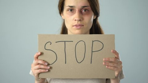 Stop word on poster in female hands, violence against women, problem awareness