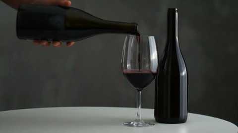 Red wine pouring into wine glass. Close up. Seamless looping cinemagraph video