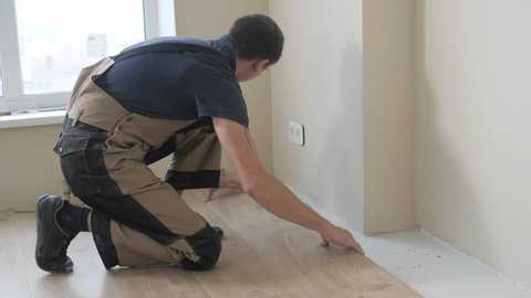 A Man Places Laminate On The Floor