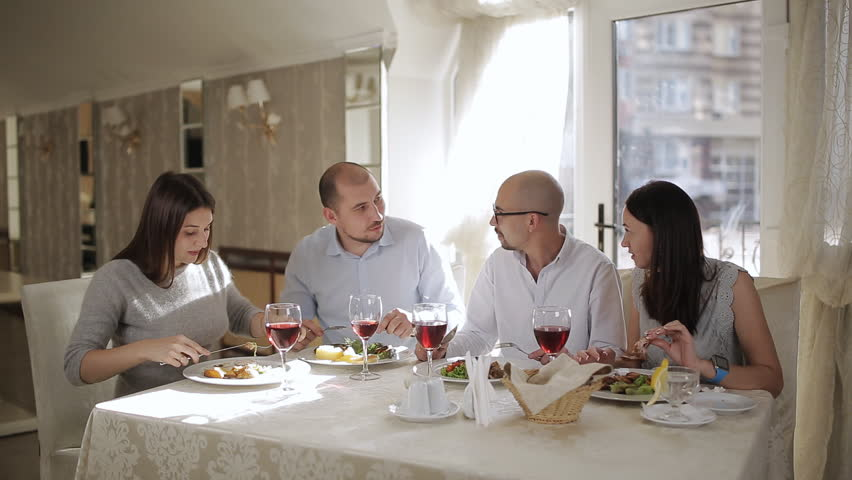 Four friends in the restaurant, eat meat and drink red wine in the glass. | Shutterstock HD Video #1019265313