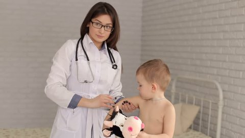 Doctor giving a child an intramuscular injection in arm. Young woman pediatrician performs a vaccination of a little boy. The boy is holding his favorite toy. Vaccination concept.