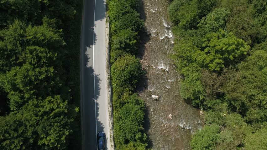 This stock footage presents an aerial view of a vehicle driving on a long, open tarmac road that runs through a thick forest. The clip can be a nice supplemental footage for movie sequences, TV shows #1019327653