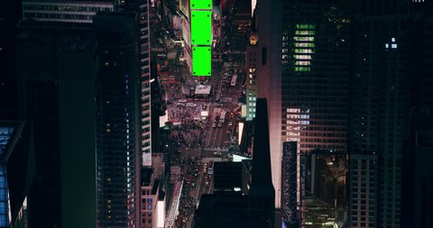 Aerial view of buildings and nightlife in Times Square in downtown Manhattan, New York City, bright night lighting. Wide shot on 4k RED camera with green screens.