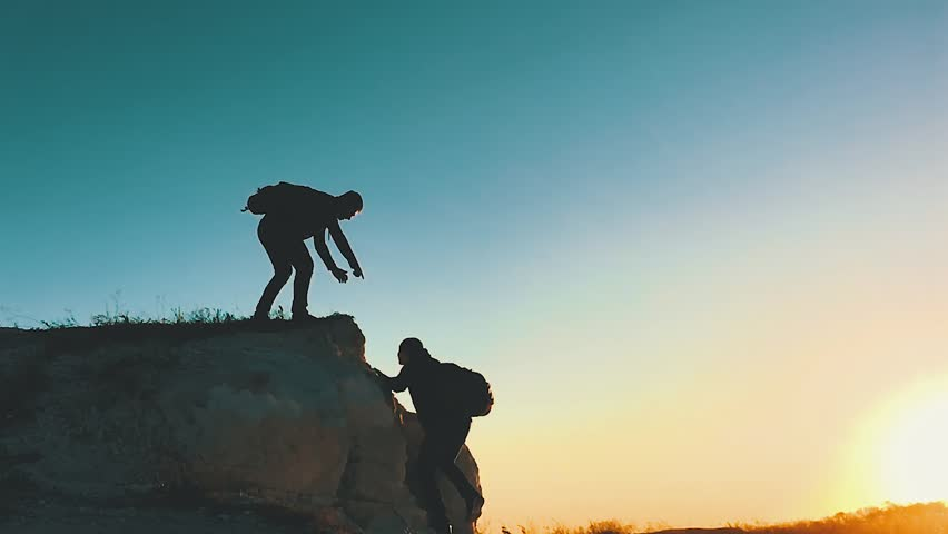 Silhouette of helping hand between two climber. two hikers on top of the mountain, a man helps a man to climb a sheer stone. couple hiking help each other silhouette in mountains with sunlight. | Shutterstock HD Video #1019381923