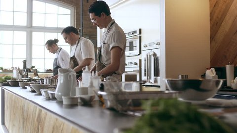 Pan shot of focused professional chefs cooking on a large counter top full of pots and tools in a kitchen with soft day lighting. Medium shot on 4k RED camera.