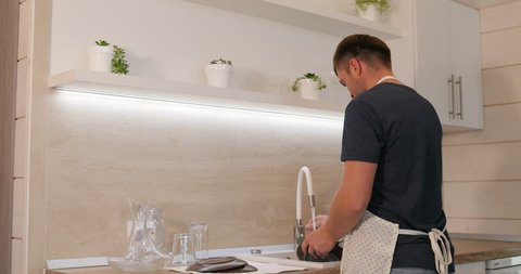 A man is washing the dishes. A happy man is washing the dishes in a beautiful bright kitchen