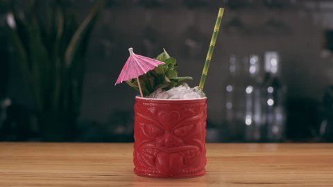 Tiki Junglebird Cocktail in a tiki glass garnished with herbs, paper umbrella and straw on a counter of bar. Close up shot on 4k RED camera.