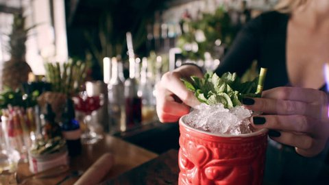 Tiki cocktail glass being decorated with little umbrella by barmaid in interior fancy bar with soft day lighting. Close up shot on 4k RED camera.