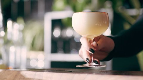 Young professional barmaid spraying a perfume spray over a bourbon sour cocktail and serving it in a fancy bar with soft interior lighting. Close up shot on 4k RED camera.