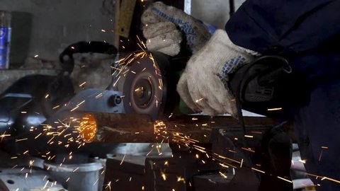 Male hand cuts off pieces of water pipe with angle grinder. Cutting of a steel with splashes of sparks at construction site. Sparks during cutting of metal angle grinder
