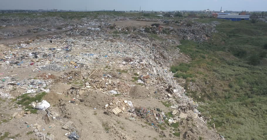 City dump in the outskirts of the city near yellow houses. The bulldozer moves along the landfill, leveling out the garbage. Gulls feeding on food waste fly over it.   Shutterstock HD Video #1019450353