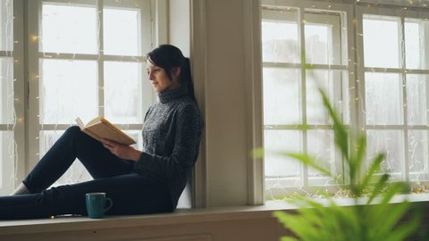 Pretty brunette in sweater and jeans is reading book sitting on window-sill on Christmas day enjoying soliture, free time and holiday. Literature and rest concept.