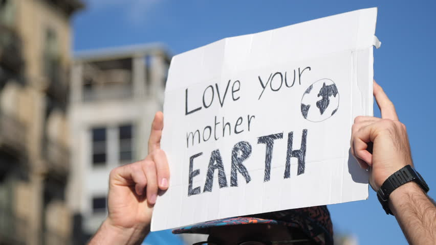 """Love your Mother Earth"" Poster on a Demonstration due to Climate Change. Activism against capitalism. Strong message on a march."