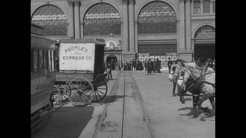 1900s: Cable cars, cars, horse drawn carriages travel around ferry building in San Francisco. People stand against building.