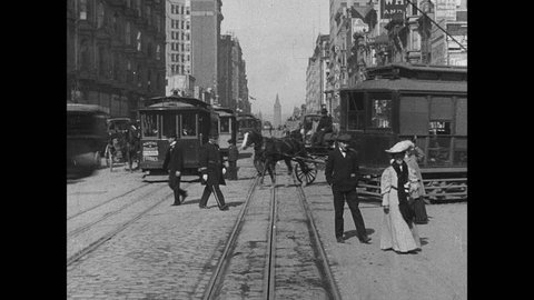 1900s: Cars and horse drawn carriages travel down city street. Cable cars travel along tracks down street. People walk around city.