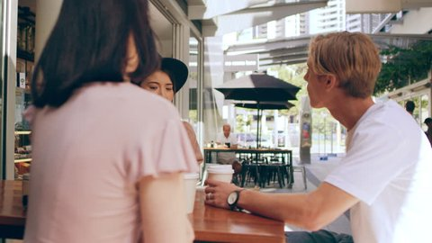 Three pretty millennial friends chat seriously and sip coffee outside a coffee shop in Australia during the day. Medium to closeup shot with 4K RED camera.
