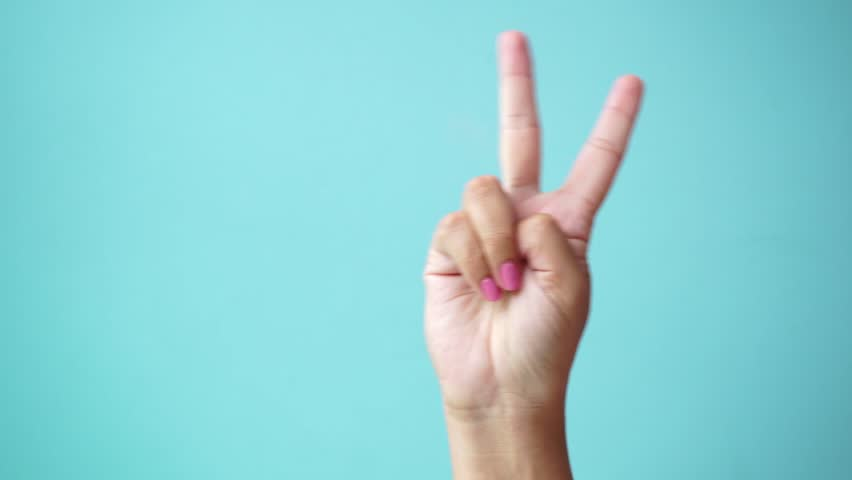 Closeup of isolated on green adult female hand counting from 0 to 5. Woman shows fist fist, then one, two, three, four, five fingers. Manicured nails painted with beautiful pink polish. Math concept.