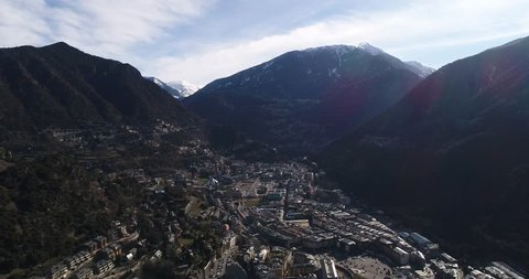 4k. Travel, drone view. Andorra. Europe. France. Fly over the mountains covered with snow. Sun shines over the summeries and blue sky. Little town between the mountains. Modern architecture