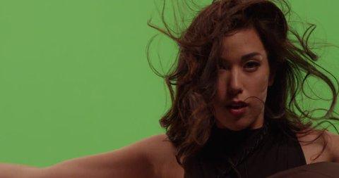Beautiful mixed race asian white woman fashion model dancer posing against green screen