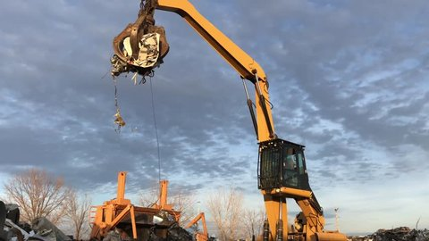Junk yard claw and crane arm high in sky with raw metal being delivered to crushing machine.
