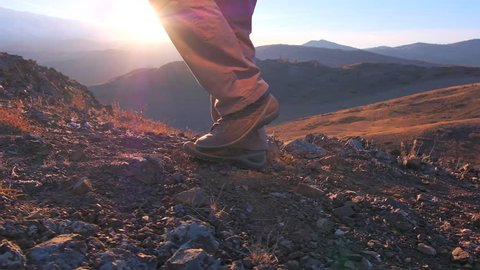 Close up of feet climber male hiker traveler man walking, climbing up in rocky top mountain at sunset. foot steps of hiker man nature travel tourism tourist hiking legs in trekking boots slow motion