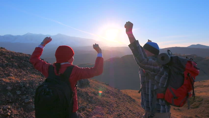 Happy tourist couple traveler hiker man woman with backpack climbing up, celebrating success on top mountain at sunset. traveler hikers with raised hands nature travel tourism hiking trekking hikers | Shutterstock HD Video #1019688823
