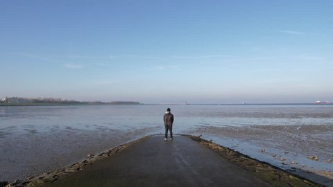Super Slow Motion man standing coast sea mud dolly shot gimbal forward 180 FPS 1920x1080 FULL HD ProRes 422 25p