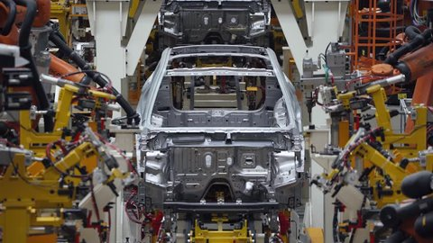 BELARUS, BORISOV - OCTOBER 19, 2017: Automobile plant, modern production of cars, car body welding process, robots, blurred view of automated production line.