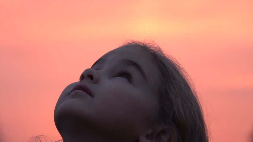 Kid looking up at the sky in nature. Little girl praying looking up at purple sky with hope, close-up.  #1019722663