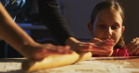 Portrait of Little Kid Looking at Mother who is rolling the dough and teaching daughter to cook learning and preparing food for family dinner in the Kitchen indoors shot on RED camera