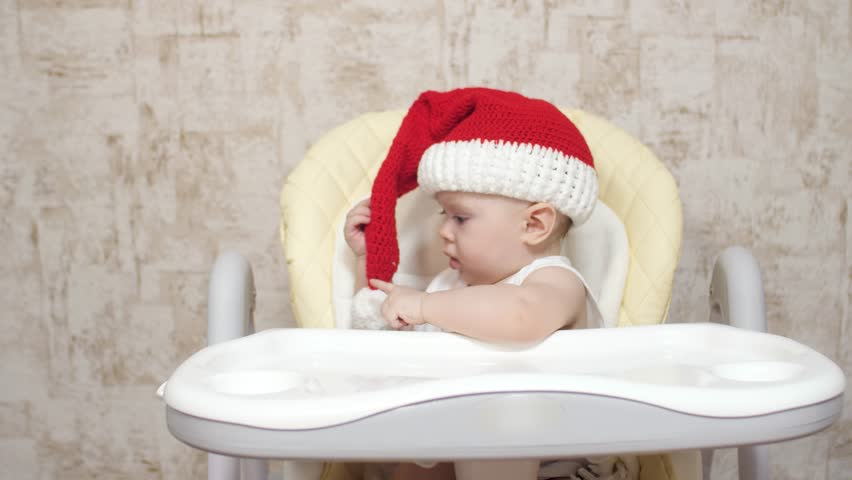 child plays in child seat in red Santa Claus hat. happy baby smiles meets  christmas. ce6fc181cf1c