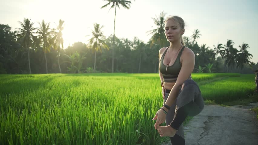 Girl do yoga extended hand to big toe pose in rice field sunny rapid slow motion