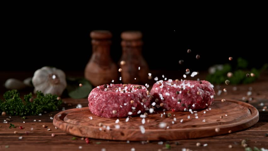 Super slowmotion footage of strewing salt and pepper at fresh raw beef meat burger, 1000fps, 4K | Shutterstock HD Video #1019786263