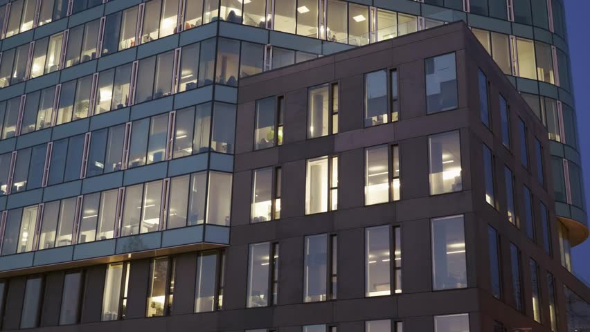 Modern multistory building facade, office center at dusk, windows with electric lighting and silhouettes of working people inside, side view, stock video   Shutterstock HD Video #1019800513